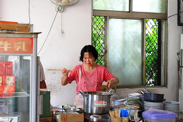 阿姨把煮好的麵條用長竹筷夾到碗裡