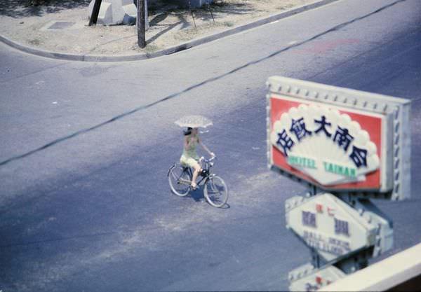 1970年,在台南大飯店的房間往街上望,看見一位撐著洋傘騎單車的妙齡女子正在穿越成功路