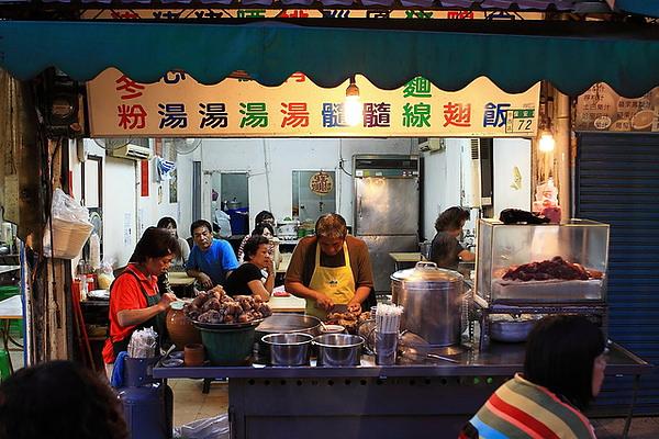 攤位,眾食客早已座定等上菜